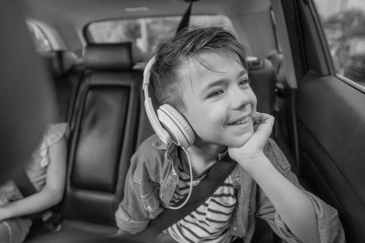Kid in car listening to music while looking out of the window