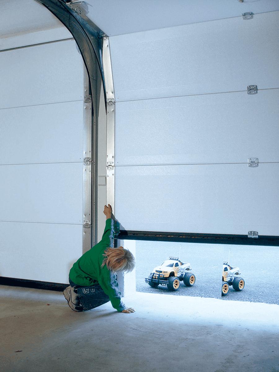 Child playing with the frame of a half-opened garage door